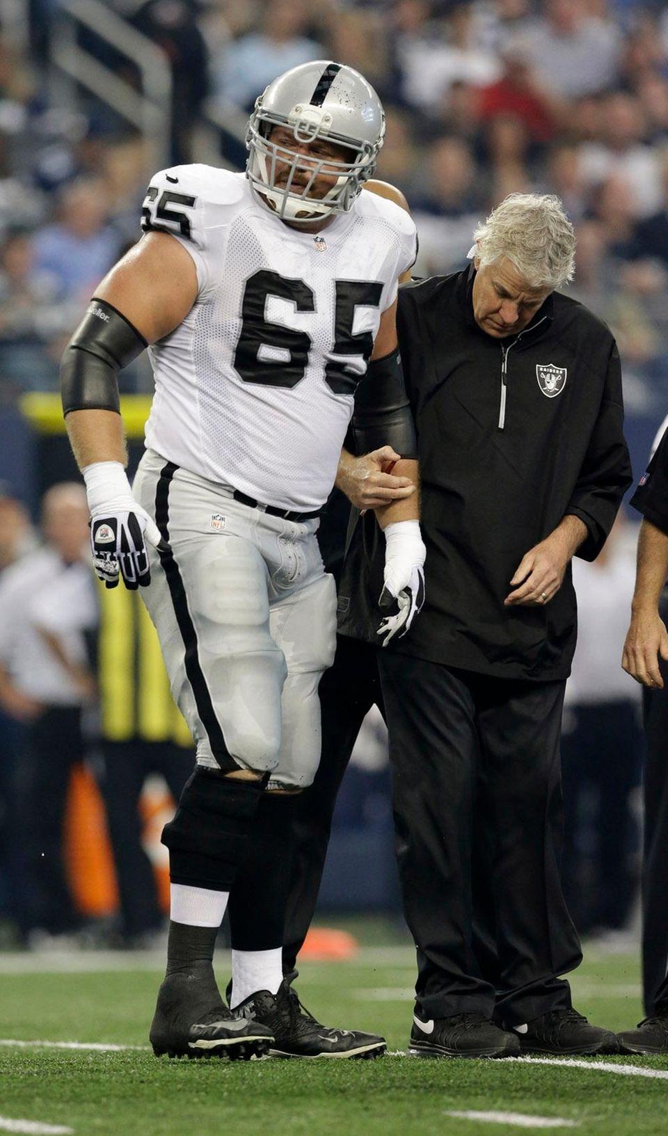 Oakland Raiders guard Mike Brisiel (65) is helped