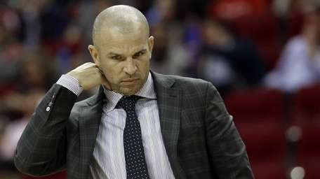 Nets coach Jason Kidd adjusts his collar during