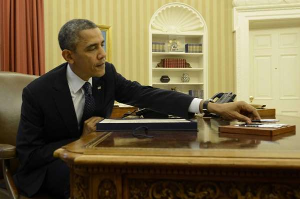 President Barack Obama grabs a pen to sign