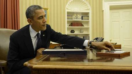 President Barack Obama grabs a pen to sign