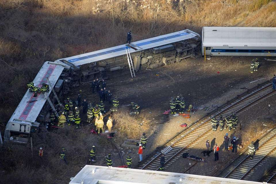 Rescuers gather Sunday morning at the derailment of
