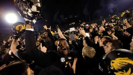 Missouri Tigers players celebrate as fans rush the