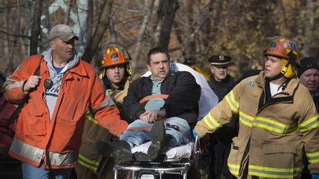 Emergency workers carry Metro-North engineer William Rockefeller away