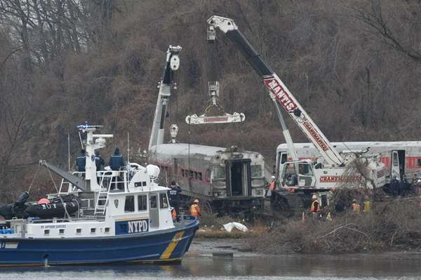 Workers right and move a derailed Metro-North train