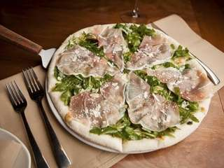 The prosciutto pizzetta is completed with fontina, arugula