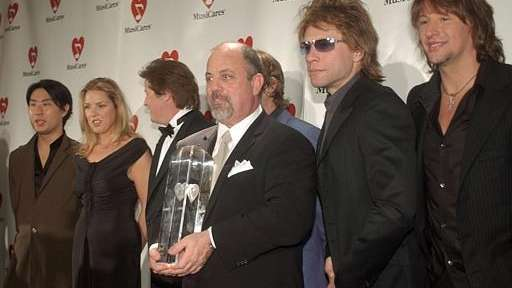 Billy Joel, center, stands with Richard Joo, far