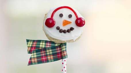 A snowman cookie pop adorned with a ribbon
