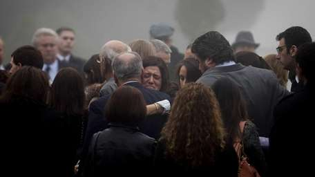 Mourners grieve following a ceremony before the casket