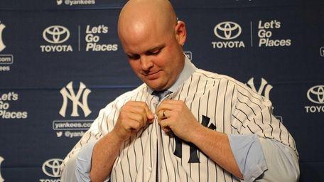 Catcher Brian McCann puts on his Yankees jersey
