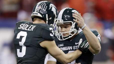 Michigan State's Michael Geiger, right, is congratulated by