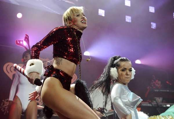 Miley Cyrus, left, performs with dancers during KIIS