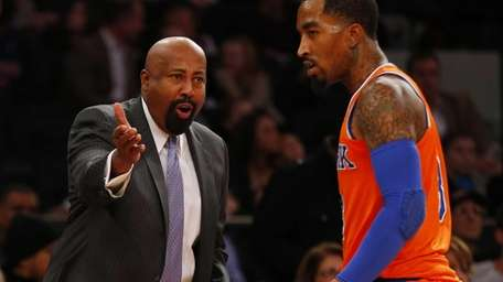 Mike Woodson speaks with J.R. Smith during a