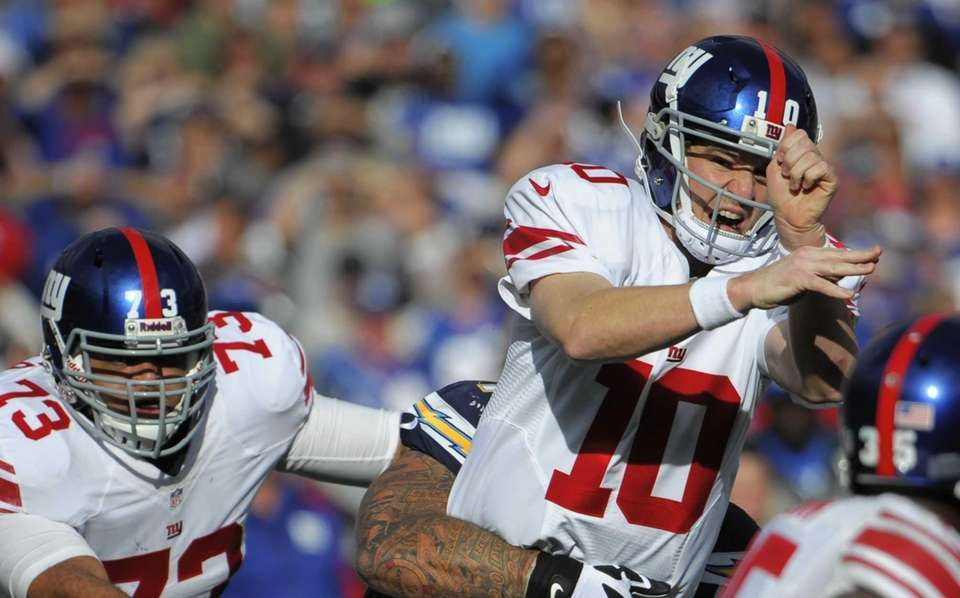 Eli Manning reacts after being hit by San