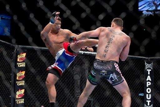 Shane Del Rosario, left, kicks Stipe Miocic during