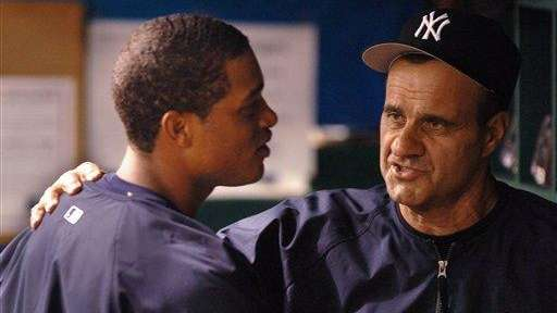 Joe Torre talks with Robinson Cano, left, in