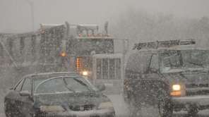 Heavy snow falls as vehicles head eastbound on