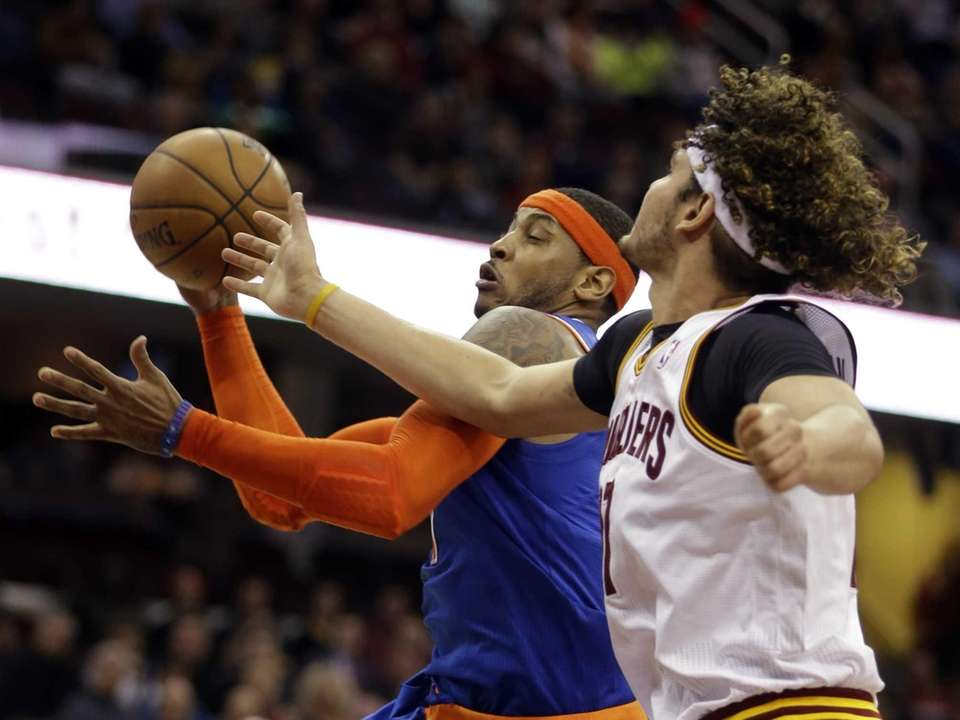 Carmelo Anthony, center, grabs a rebound against the