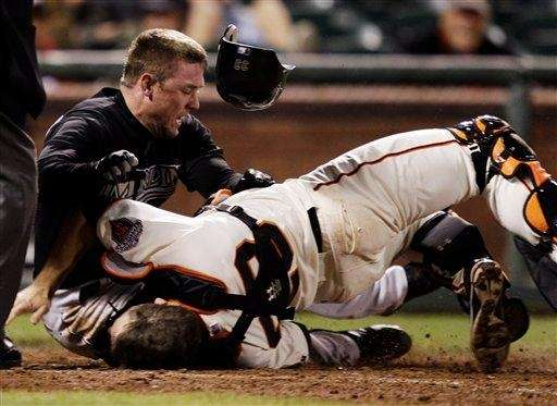 The Florida Marlins' Scott Cousins, top, colliding with
