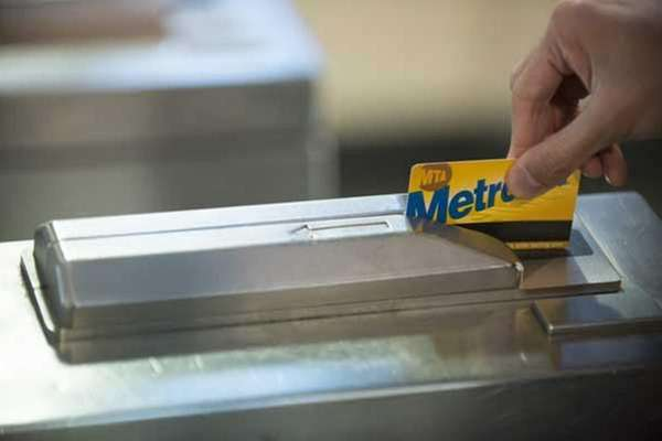 Subway riders use their Metrocards to enter the