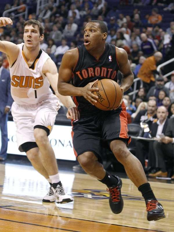 Toronto Raptors point guard Kyle Lowry, right, drives