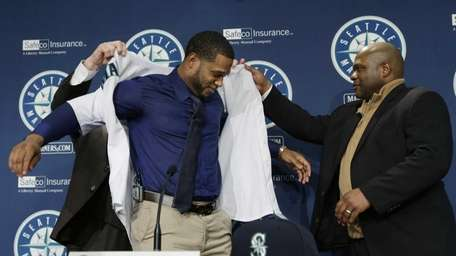 Robinson Cano, center, is helped into his new