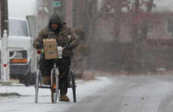 A man rides a tricycle as snow starts