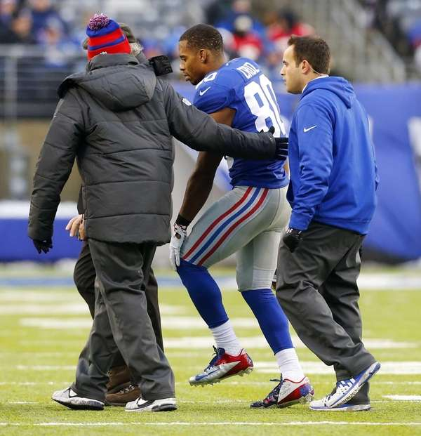 Victor Cruz is helped off the field during