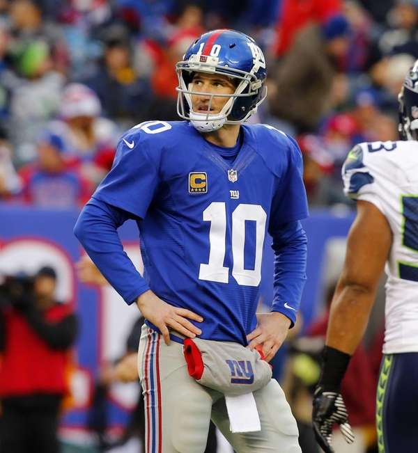 Eli Manning looks on as he walks back