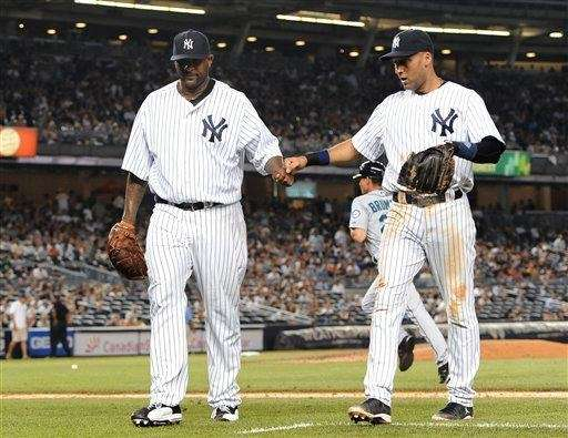 Derek Jeter, right, bumps fists with CC Sabathia