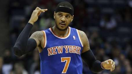 Carmelo Anthony reacts after making a three-point basket