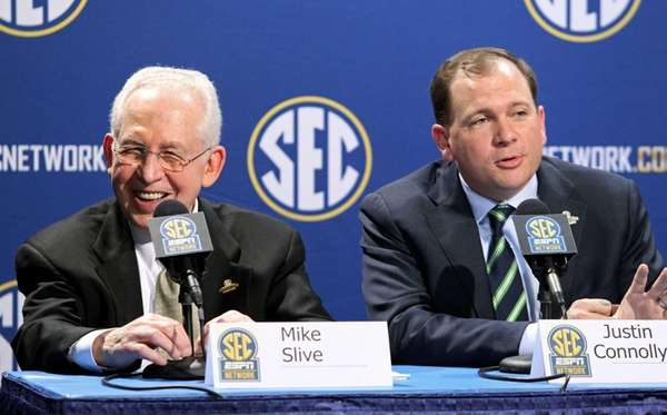 Southeastern Conference Commissioner Mike Slive, left, laughs as