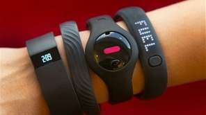 Four fitness trackers are shown in this photograph.