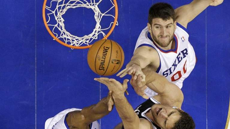 Nets' Brook Lopez, center, goes up for a