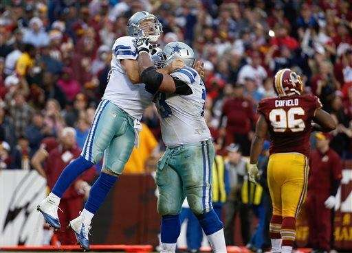 Dallas Cowboys quarterback Tony Romo, left, is hugged