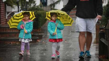 Protected from the steady rain, 4-year-old twin sisters