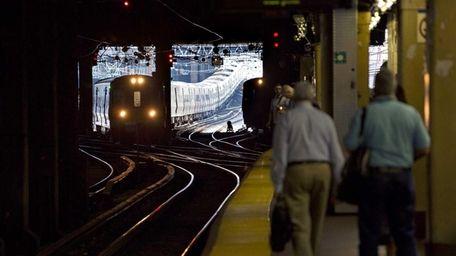 LIRR commuters wait on a platform at Penn