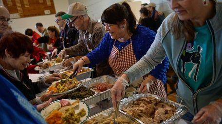 Ellie Viglass, of Greenlawn, serves people food as