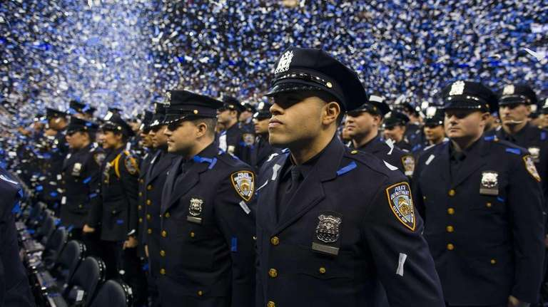 Newly sworn-in NYPD officers stand at attention as