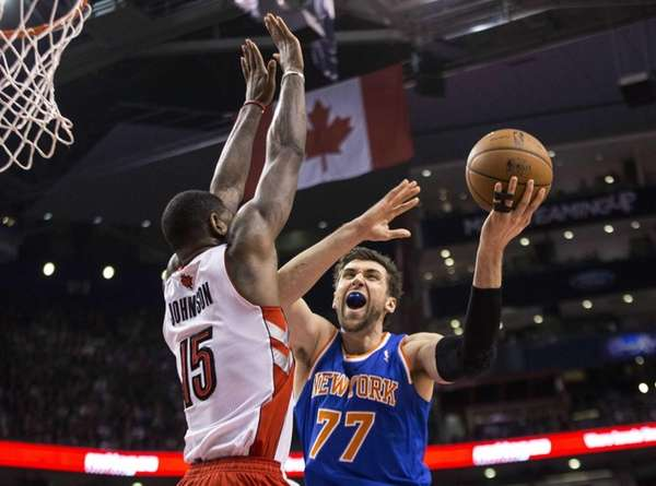 Knicks' Andrea Bargnani, right, shoots on Toronto Raptors'