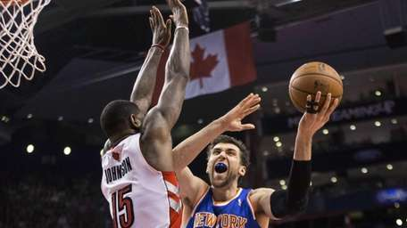Knicks' Andrea Bargnani, right, shoots on Toronto Raptors'