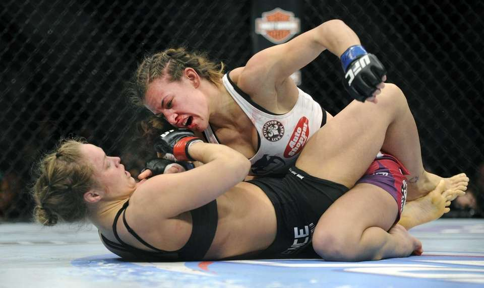 Miesha Tate, top, punches Ronda Rousey during the