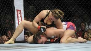 Ronda Rousey, top, punches Miesha Tate during the