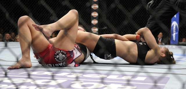 Ronda Rousey, right, holds Miesha Tate during the