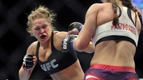 Ronda Rousey, left, punches Miesha Tate during the