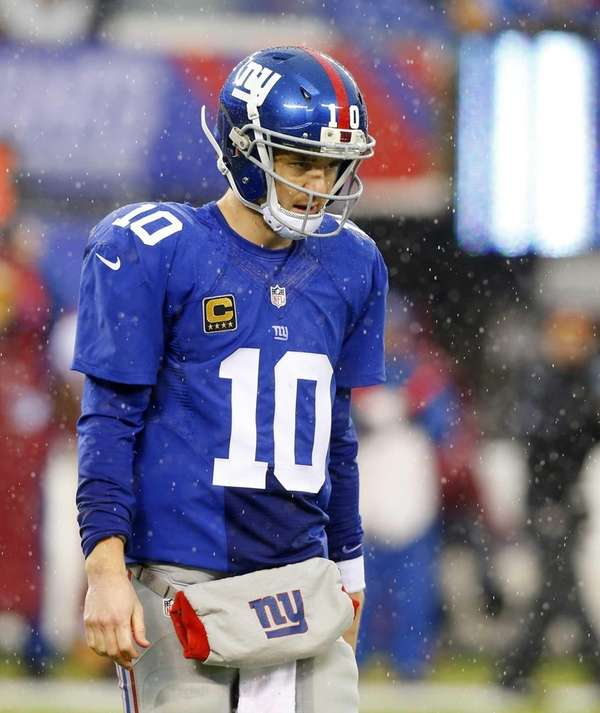Eli Manning walks to the bench after a