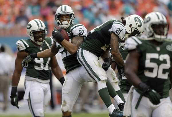 Dee Milliner (27) celebrates with teammates after intercepting