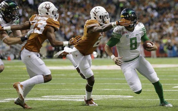Oregon's Marcus Mariota is chased by Texas' Mykkele