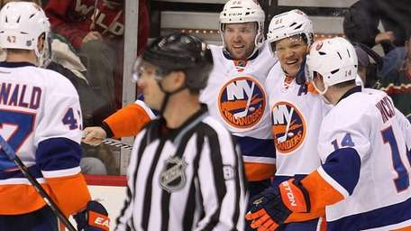 Kyle Okposo, second from right, is congratulated by