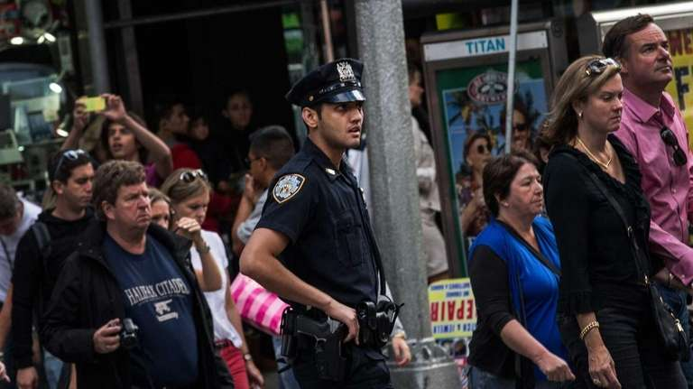 An NYPD officer walks with a crowd in