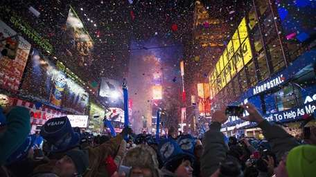 Revelers cheers under falling confetti at the stroke